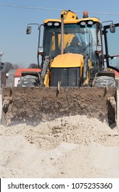 Tracktor working with a sand at the construction site.