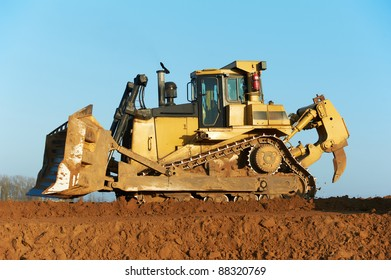 track-type bulldozer machine doing earthmoving work at sand quarry