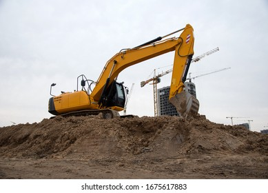 Track-type excavator during earthmoving at construction site. Backhoe digging the ground for the foundation and for laying sewer pipes district heating. Earth-moving heavy equipment