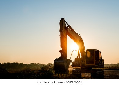 Track-type loader excavator machine doing earthmoving work at construction site on sunset background