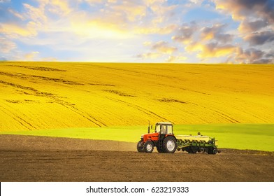 Tractor  agrimotorworking the ground. Different parts of the field, green yellow, black. Beautiful sky, hilly terrain. Season of agricultural works.