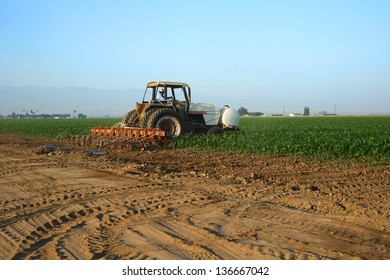 A tractor applies agricultural chemicals to a field of corn in Central California