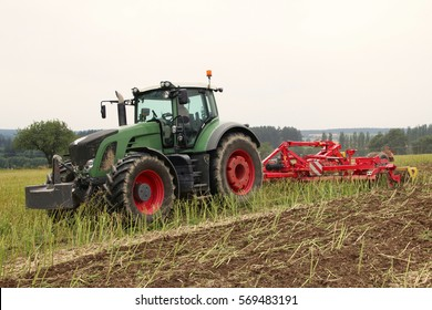 Tractor with attached tilling tool preparing field with rape stubble for fertilizing and seeding of wheat certified as bio agriculture, frontal perspective, cloudy autumn day