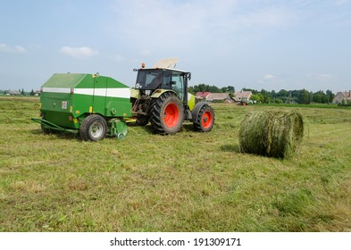 tractor bailer collect hay in field. Agricultural machine making hay bales. Seasonal rural works.