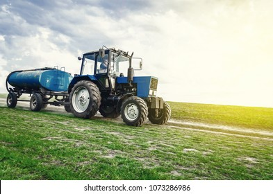 tractor of blue color with a barrel trailer rides along the spring field along the road. Successful farming.