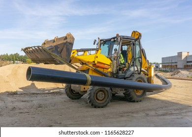 Tractor carries a long pipe for water supply at the construction site