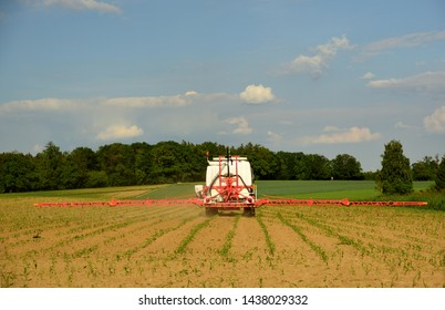 a tractor carries poison on a field with corn plants