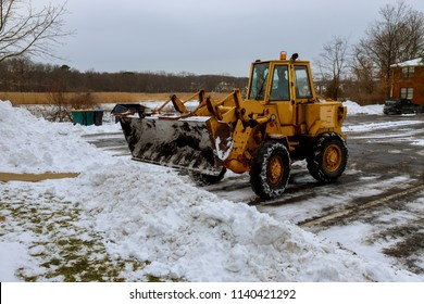 Tractor cleaning snow at city street and a parking lot after snowfall
