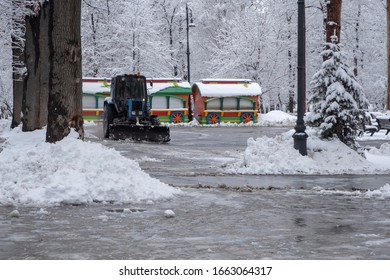 Tractor is cleaning snow in park. Tractor is sweeping snow in snowfall. - Shutterstock ID 1663064317
