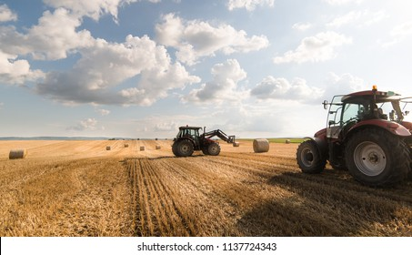 A tractor collecting straw bales in a harvested field