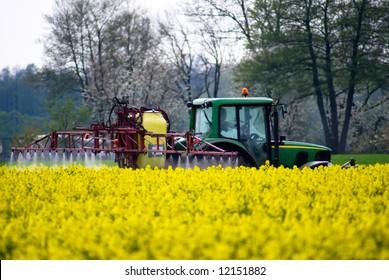 Tractor crop spraying with fertilizer onto field