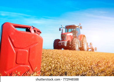 Tractor cultivating in the field with gas can petrol, diesel, bio fuel. Agriculture and farming.