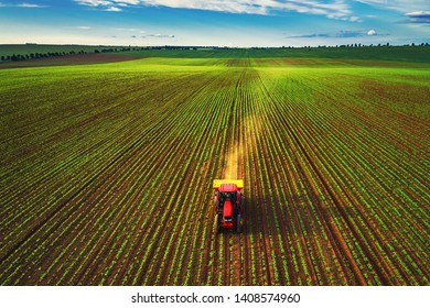 Tractor cultivating field at spring, aerial top view