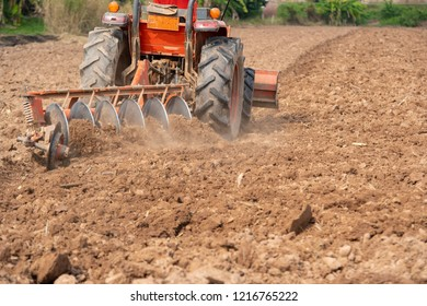 Tractor cultivating field at spring,Tillage is the agricultural preparation of soil by mechanical agitation of various types in early spring season of agricultural works at farmlands.