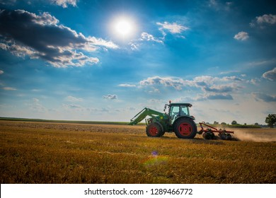Tractor with a cultivator plowing a field in autumn, under the sun