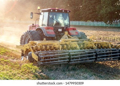tractor cultivator plows the land, prepares for crops. dust on field