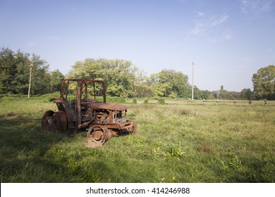 tractor destroyed by fire in a grass field in the summer close up