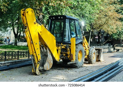 Tractor digger is parked on the sidewalk. It is used for digging ground for laying new water pipes in the city.