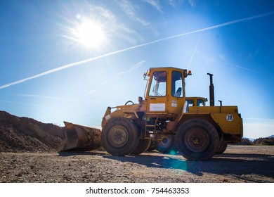 A tractor excavator in the sun. Yellow machine waiting for next duties.