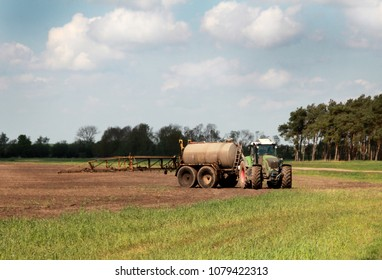 tractor with fertilize tank spreading manure on a field