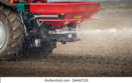 Tractor and fertilizer spreader in field