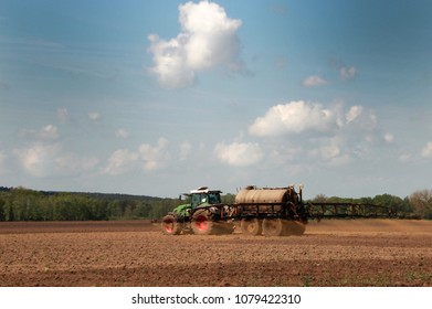 tractor with fertilizer tank spreading manure on a field