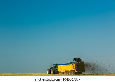 the tractor fertilizes the field with manure. A large trailer. Sowing. Agroindustry.Pole before sowing. Against the sky. yellow tractor.