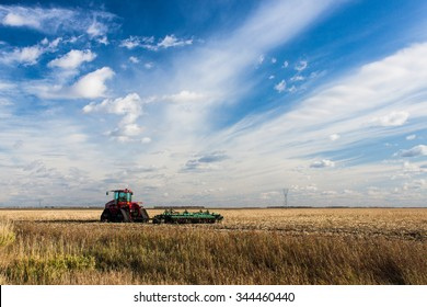 Tractor in Field with Blue Streaky Sky