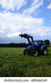 Tractor in a field cutting the grass to make hay on 4th August 2017, in Chapel St Leonards, near Skegness, Lincolnshire
