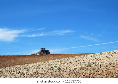 Tractor in the field, plowing a plot in summer.