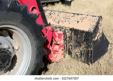 Tractor front end loader with dirt on construction side, focus on the wheel