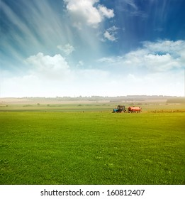 tractor in green field over blue cloudy sky gather crops in summer or autumn