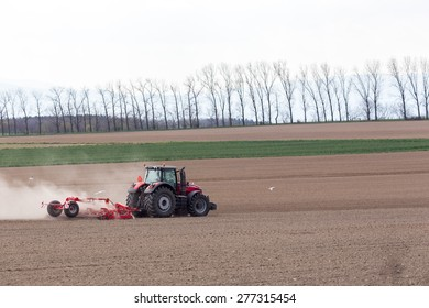 The tractor harrowing the large brown field in spring season