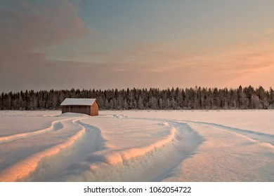 The tractor has visited an old barn house on a snowy field in the rural Finland. The setting sun colors the landscape amber.
