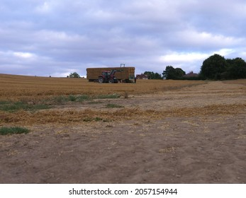 Tractor and hay bales at harvest time in Autumn wide shot