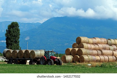 Tractor with hay trailer next to a large stack of round hay bale in a plan under the Alps