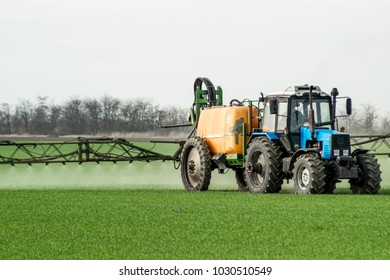 Tractor with high wheels is making fertilizer on young wheat. The use of finely dispersed spray chemicals. Tractor with a spray device for finely dispersed fertilizer.