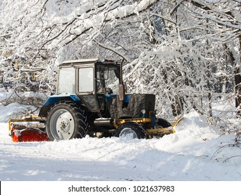 Tractor, with large wheels, to clean snow with a brush and scraper stands outside cold winter and white snow around