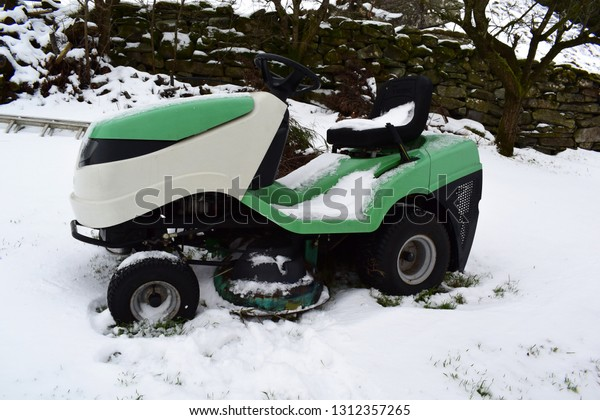 Tractor - lawn mower stands in the snow. Garden tools.