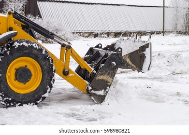tractor loader cleans snow after a snowfall