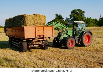 tractor loading hay bales on a trailer