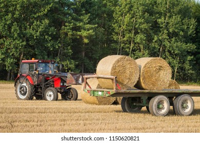 The tractor loads bales of hay onto the trailer. Agricultural machinery on the field after harvesting grain crops.