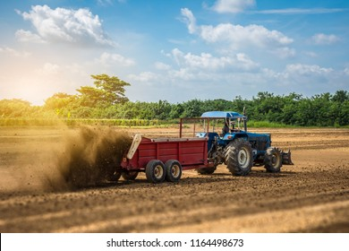 The tractor with the manure spreader working in the field
