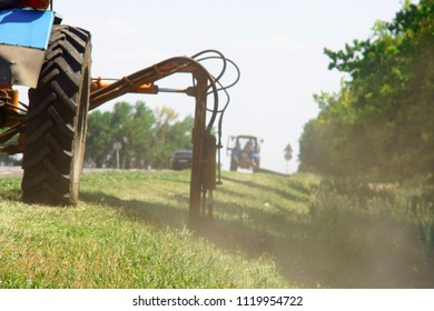 Tractor with a mechanical mower mowing grass on the side of the asphalt road