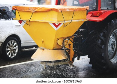 Tractor with mounted salt spreader, road maintenance - winter gritter vehicle.  Tractor de-icing street, spreading salt. Municipal service melting ice on streets. Diffuser of salt blend on road
