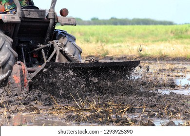 tractor moves through a wet puddle mud black, tractor ploughing at rice field and splash of muddy wet, mud from a tractor in plowing rice field, a large amount of water mud and splashes under wheels