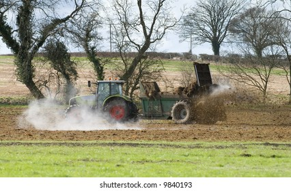 Tractor muck spreading during late winter, steam from the manure