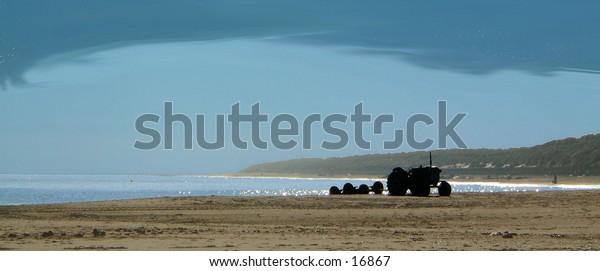 Tractor on the beach under a leaden sky
