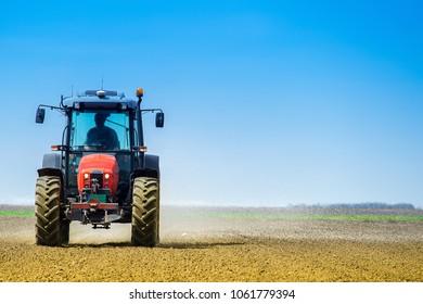 Tractor on the field spreading fertilizer in the early spring time. Fertilization of soil in the early spring time.