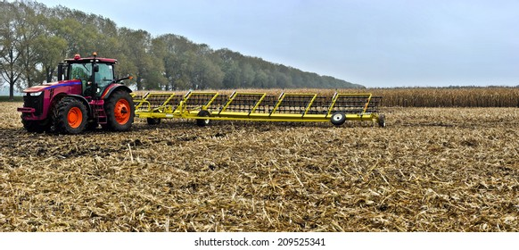 tractor on the field with wide-Tine Harrow